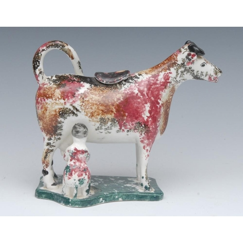 8 - A 19th century cow creamer and cover, standing four square, with milkmaid, sponged in ochre, puce an...