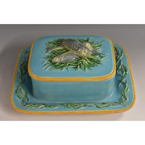 8A - A Minton Majolica rounded rectangular sardine box, the cover moulded with three fish on a bed of sea...