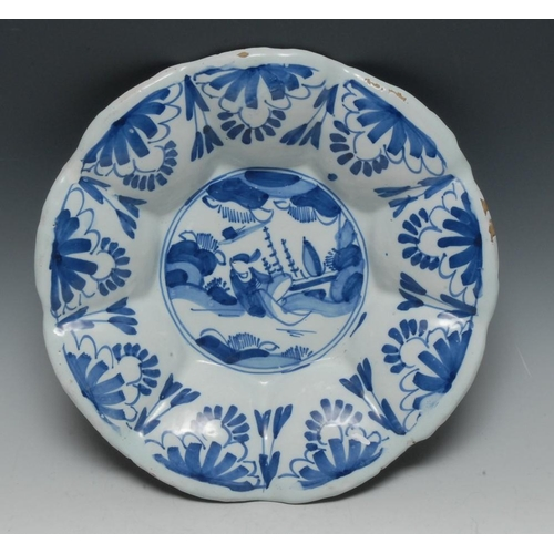 14 - A Delft lobed circular dish, decorated in underglaze blue with stylised figure and foliage, 31cm dia...
