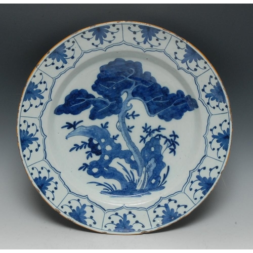 4 - An 18th century Delft charger, painted in tones of blue in the Chinese taste with a prunus tree and ...