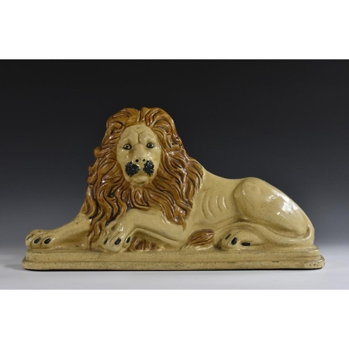 5 - A substantial 19th century salt-glazed stoneware door porter, as a recumbent lion, naturalistically ...