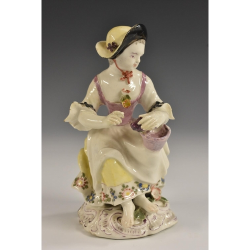 52 - A Bow figure, Allegorical of Autumn, of a girl seated holding a bowl of grapes, 13cm high, c.1760...