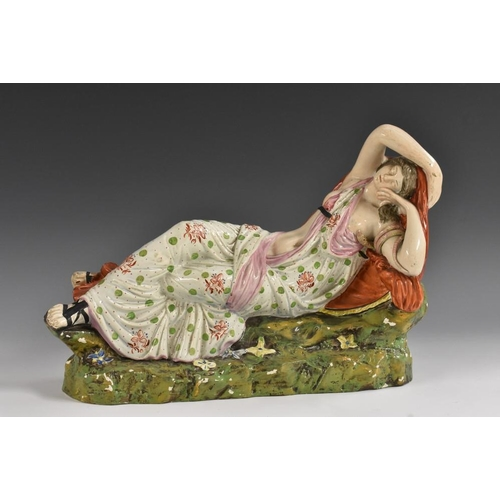 6 - A Staffordshire Pearlware figure, Cleopatra/Ariadne, reclining wearing a flowing chiton painted with...