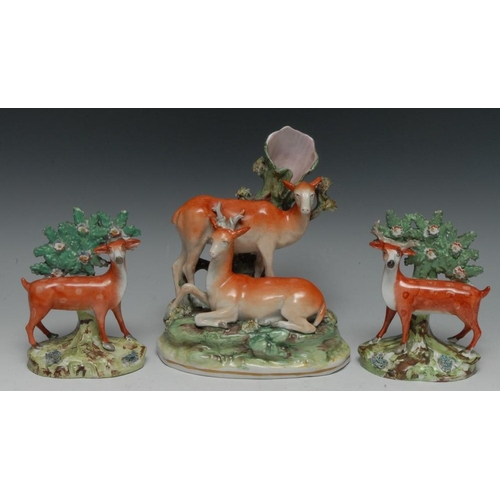 8 - A pair of mid 19th century Staffordshire Pearlware models, of spotted stag and deer, standing to the...