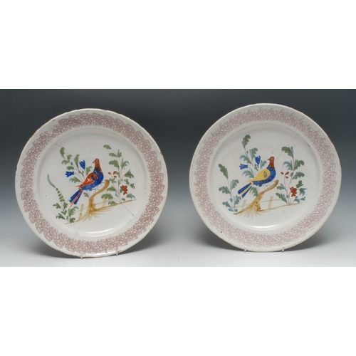 9 - A pair of 19th century circular plates, painted with stylised birds, purple sponged border, 32cm dia...