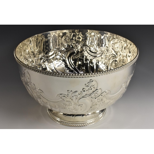 3 - A large Victorian style E.P.N.S pedestal punch bowl, half wrythen-fluted and embossed with scrolling...