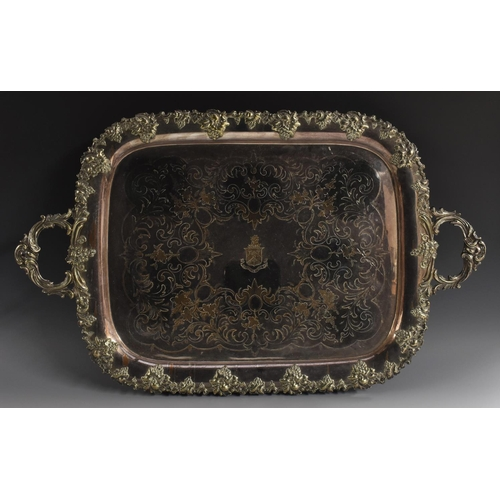 4 - A large Victorian two-handled serving tray, the field engraved and chased with crest and scrolling f...