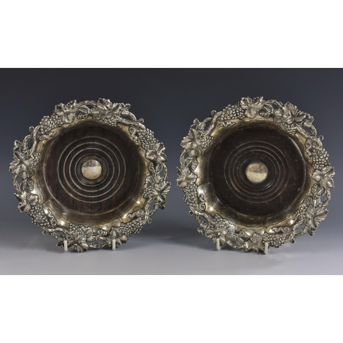 5 - A pair of post-Regency Sheffield plate fluted shaped circular wine coasters, fruiting vine borders, ...
