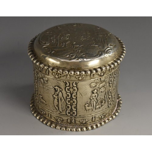 59 - A Dutch silver circular box and cover, chased with figures in 18th century dress, domed push-fitting...