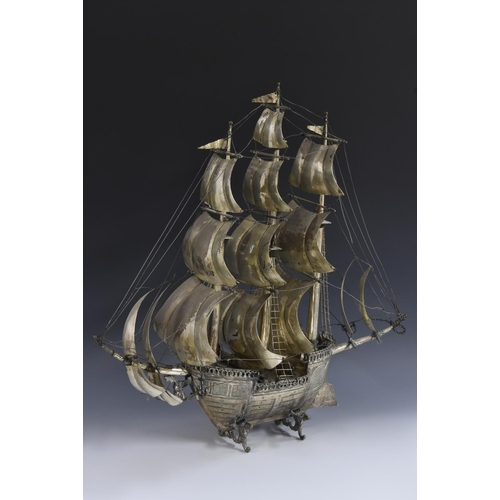 9 - A large Continental silver coloured metal nef, the three masts with billowing sails, figures on deck...