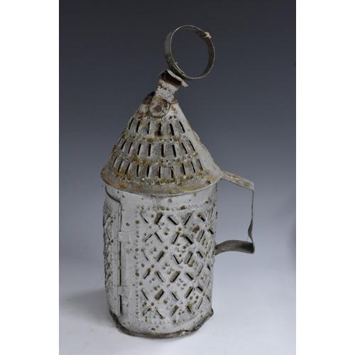 3079 - A 19th century vernacular tin candle lantern, conical canopy, hinged door, angular handle, pierced t...