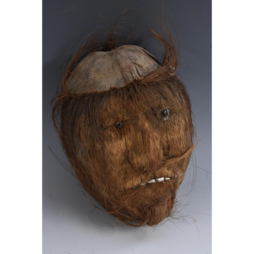 3436 - Folk Art - a coconut, in the rough, carved and decorated with a comical face, 21cm long...