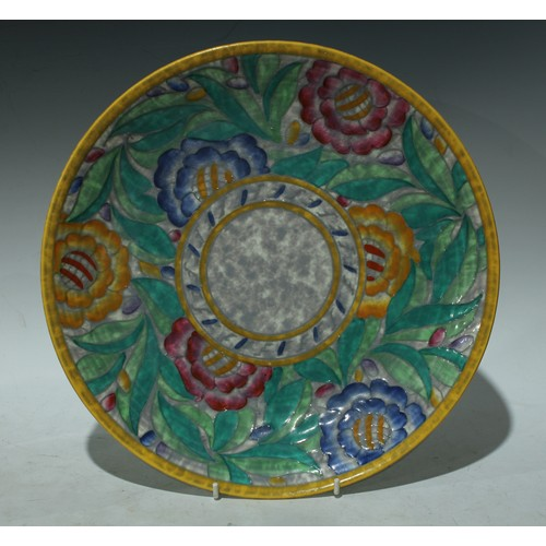 21 - A Crown Ducal Charlotte Rhead circular plate, tube lined with large flowerheads in pink, yellow and ...