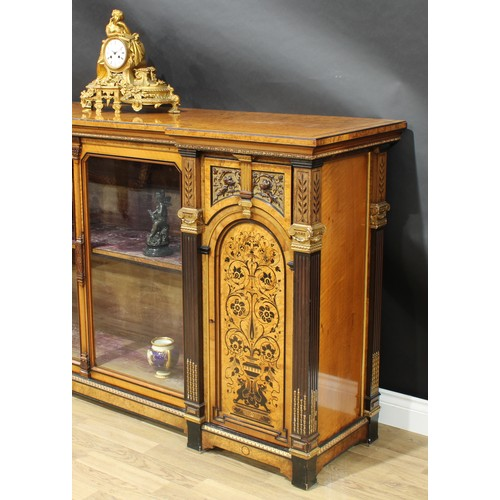 6 - A Victorian parcel-gilt amboyna and marquetry inverted break-centre library side cabinet, in the man...