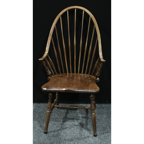 11 - A spindle back kitchen chair, saddle seat, turned supports, 104cm high...