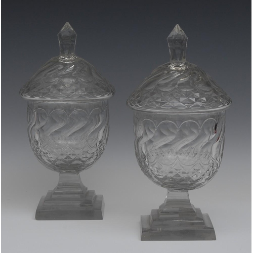 13 - A pair of 19th century clear glass sweetmeat urns and covers, faceted knop finials, stepped square b...