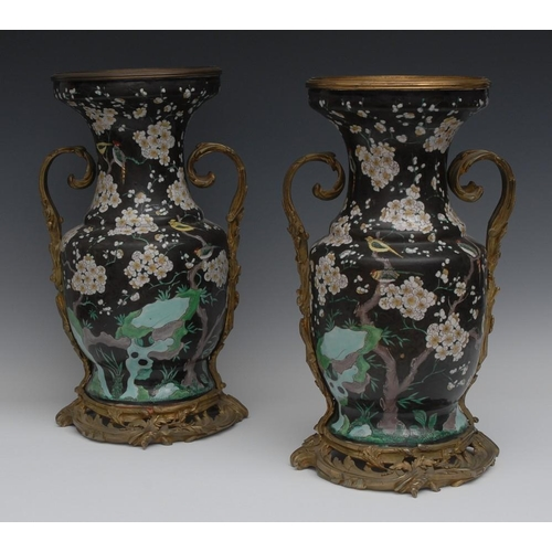 21 - A pair of large ormolu mounted Chinese Famille Noir ovoid vases, each painted with birds perched on ...