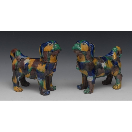 24 - A pair of Chinese models of dogs, each standing four square, with tail curled, glazed in mottled ton...