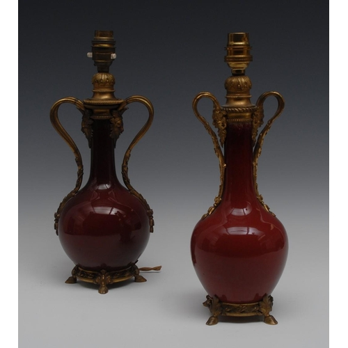 29 - A near pair of ormolu mounted Chinese sang de boeuf bottle vases, divided loop handles terminating i...