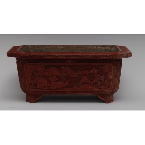 33 - A Chinese cinnabar lacquer shaped rectangular bough pot, carved in relief with fishermen, chrysanthe...