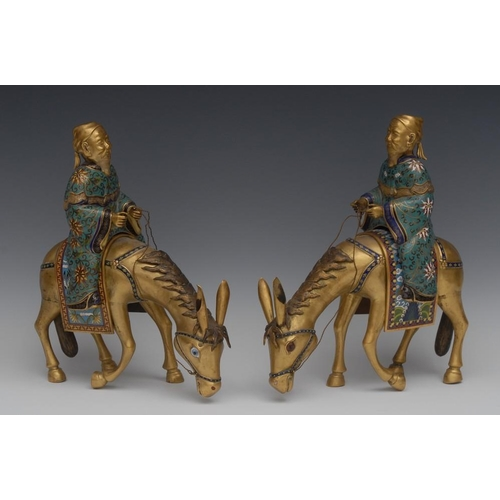 34 - A pair of 19th century Chinese cloisonne models of scholars riding donkeys, each gilt and brightly d...