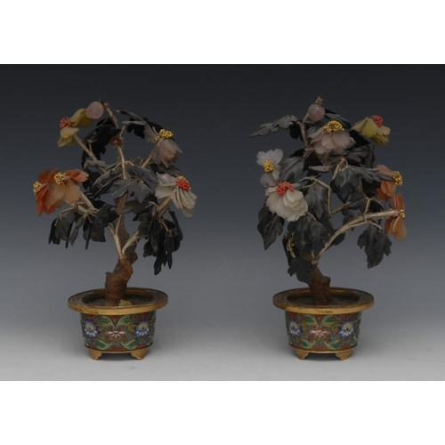 37 - A pair of Chinese hardstone trees, the circular cloisonne enamel pots decorated in polychrome with s...