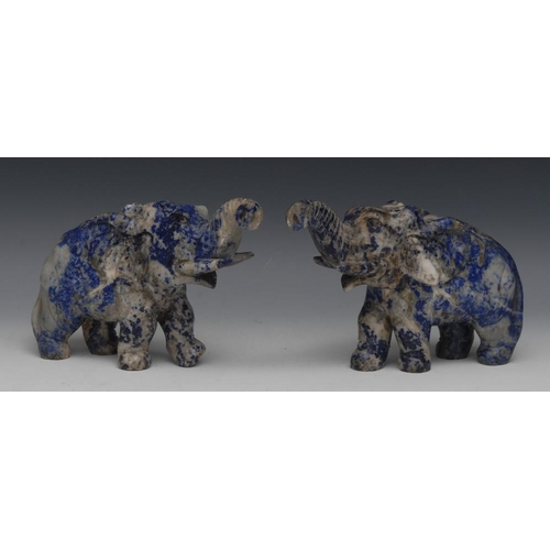 38 - A pair of lapis lazuli carvings, of elephants, each with trunk raised, striding forward, 15cm high...