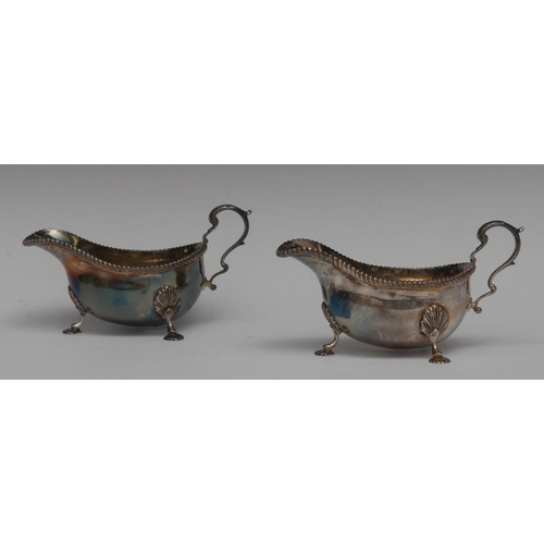 49 - A pair of George III design silver sauce boats, acanthus capped flying-scroll handles, shaped pad fe...