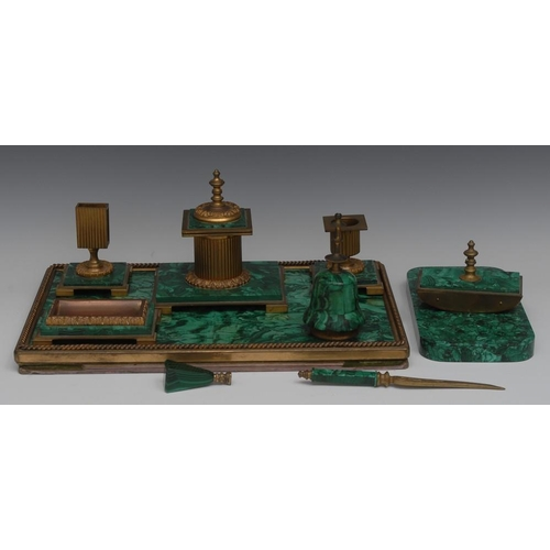 71 - A composed malachite desk suite, comprising a combination tray and blotting pad, an inkwell, a candl...