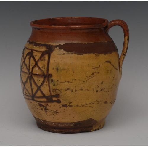 19 - An 18th century slipware jug,  with geometric motif in brown on an ochre ground, strap handle,  15cm...