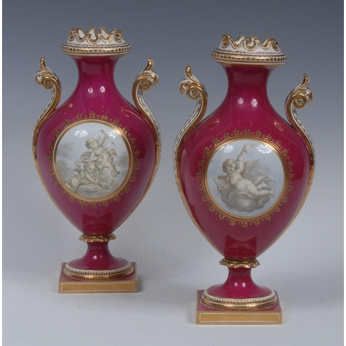 54 - A pair of Coalport pedestal ovoid vases, decorated in the Wateauesque manner with cherubs within a g...