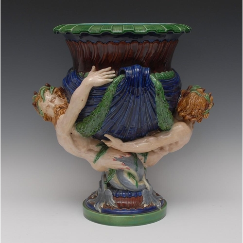 9 - A Minton majolica Mermen and Laurel jardiniere, the vase with everted rim and laurel swags supported...
