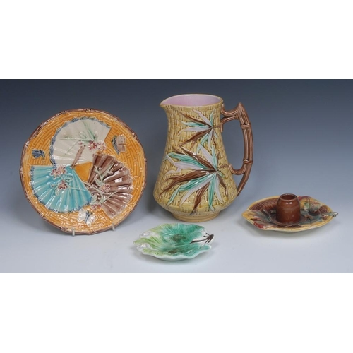 13 - A Victorian majolica jug, in relief with bamboo, in tones of pink, green and brown, on a yellow bask...