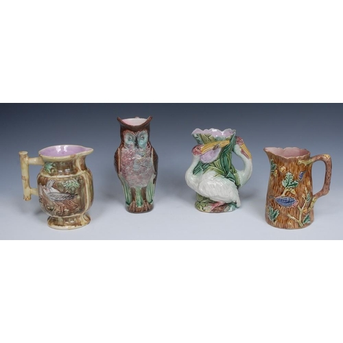 14 - A Victorian majolica jug, moulded in relief with two storks, amongst reeds, in tones of pink, green ...