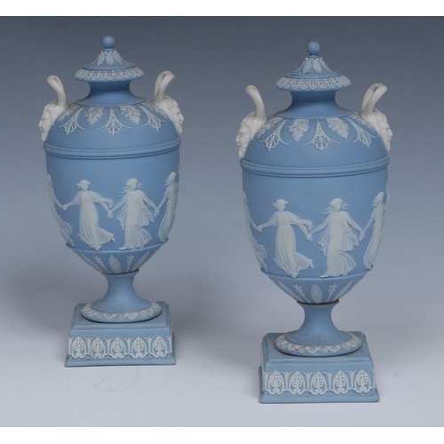 22 - A good pair of Wedgwood Jasperware pedestal ovoid vases and covers, typically sprigged in white with...