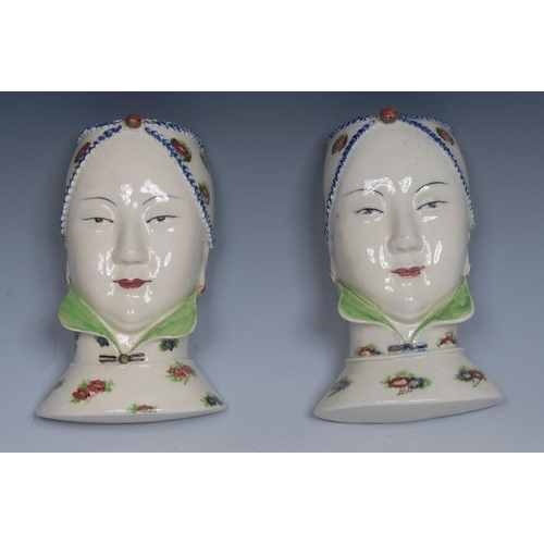 6 - A pair of figural wall pockets, each modelled as an Oriental lady, sponged with flowers and decorate...