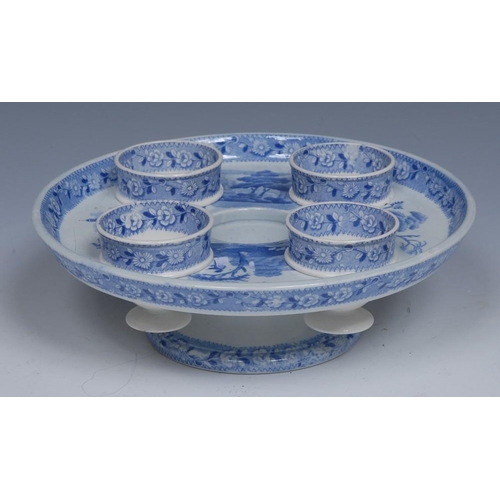 62 - A Spode egg cup stand and four cups, transfer printed in tones of blue with mausoleum, trees and fol...