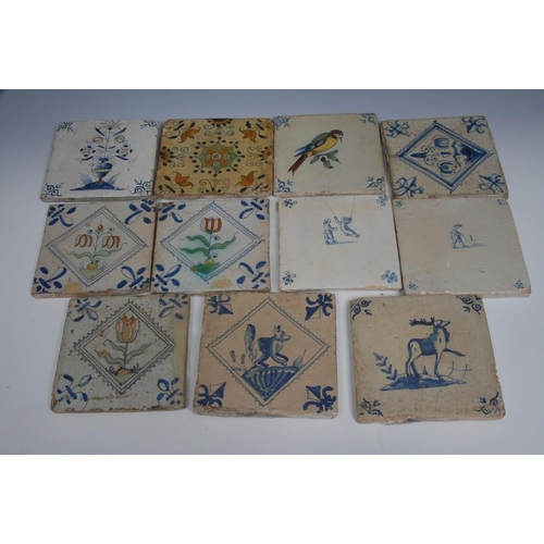 9 - <p>A set of three Dutch polychrome square tiles, painted with a stylised tulip, the angels with coba...
