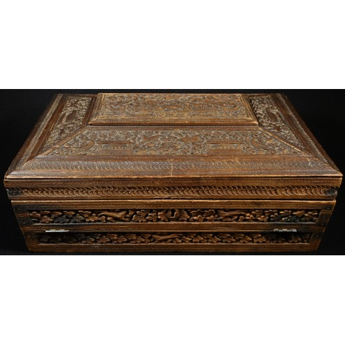 5039 - A 19th century Indian sandalwood sarcophagus combination work and writing box, profusely carved with...