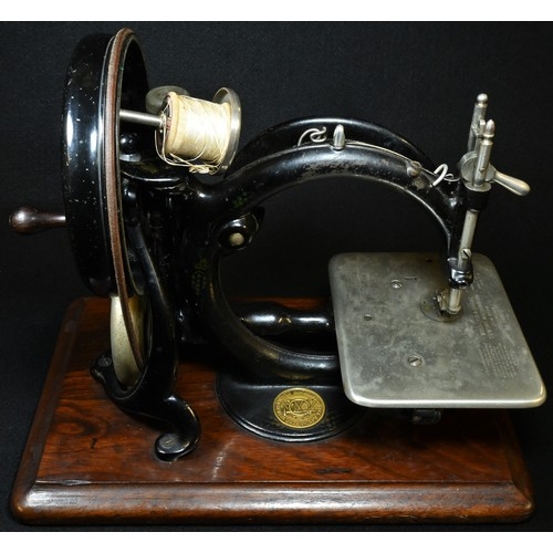 5008 - A 19th century American C-frame sewing machine, by Willcox & Gibbs, New York, wooden base, 33cm wide...