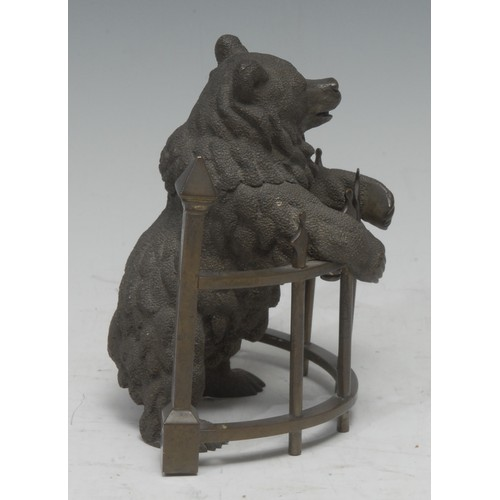 5059 - A 19th century Russian brown patinated bronze novelty inkwell, as a bear standing at railings, his h...