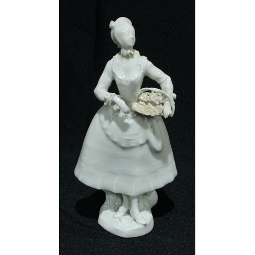 26 - A Vienna figure, in the white, of a lady, holding a basket, 16cm high, Beehive mark