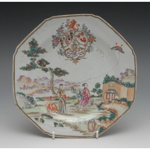 21 - A Chinese Famille Rose Armorial octagonal plate, painted with figures in a garden, flying a kite, 22...