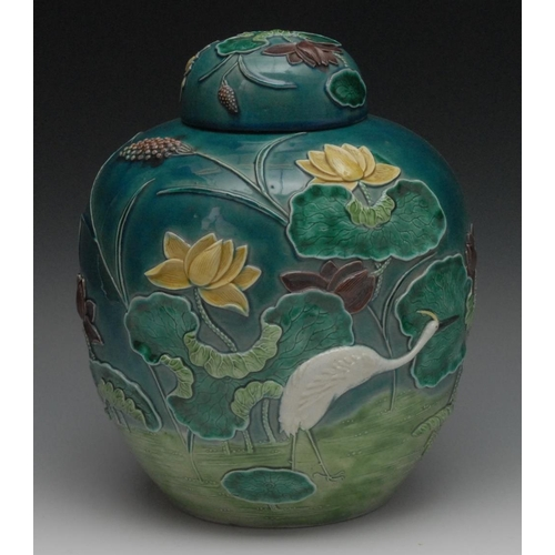31 - A Chinese ovoid ginger jar and cover, decorated in high relief with a crane amongst water lilies, co...