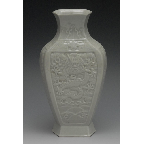 33 - A Chinese pale celadon flattened ovoid vase, moulded with a fierce dragon above the waves, spreading...