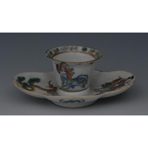 38 - A Chinese porcelain flared wine cup and quatrefoil stand, painted in polychrome enamels with a femal...