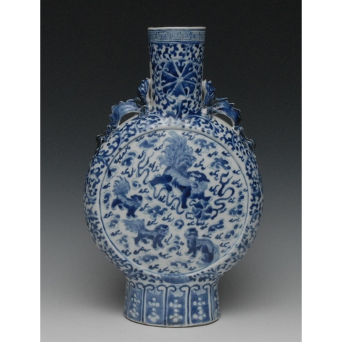 39 - A Chinese porcelain moon flask, painted in underglaze blue with temple lions and scrolls, dragon han...