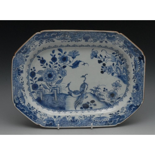 48 - An 18th century Chinese canted rectangular blue and white meat plate, painted with peacocks, peonies...