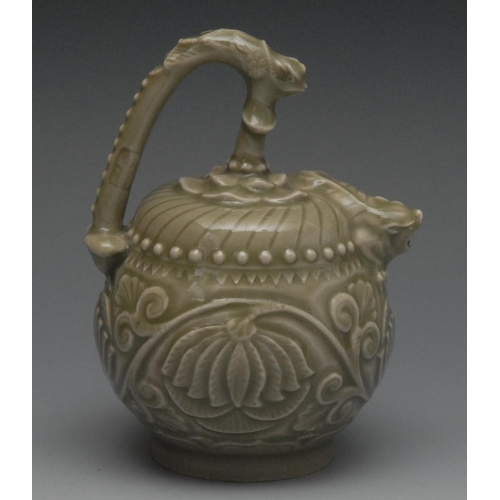 57 - A Chinese celedon globular water dropper, in relief with lotus, mystical beast spout, high handle, 1...