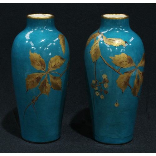 23 - A pair of French faience slender ovoid shoulder vases, hand painted with leaves and berries in gold ...